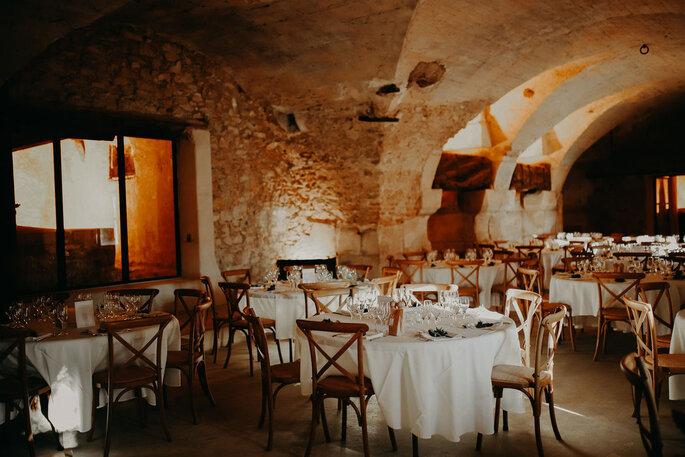 Des tables aux nappes blanches et des chaises en bois attendent les invités dans une pièce voûtée d'époque