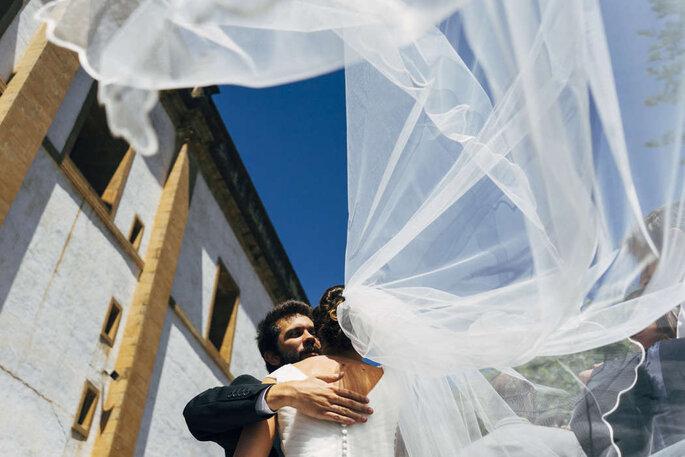 Noiva com véu a esvoaçar noivos abraçados