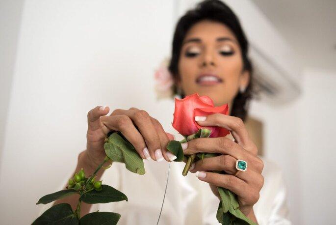 Novia sosteniendo una rosa en su mano