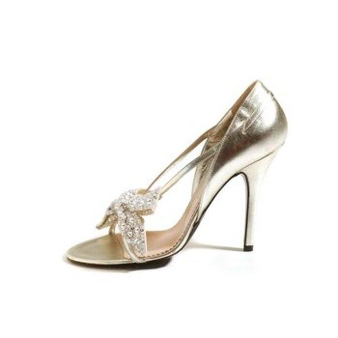Zapato tipo sandalia con talón cerrado. En plata con detalles al frente