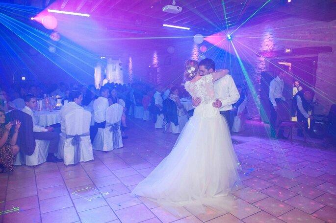 Un couple de mariés en train de danser un slow sous la lumière des projecteurs