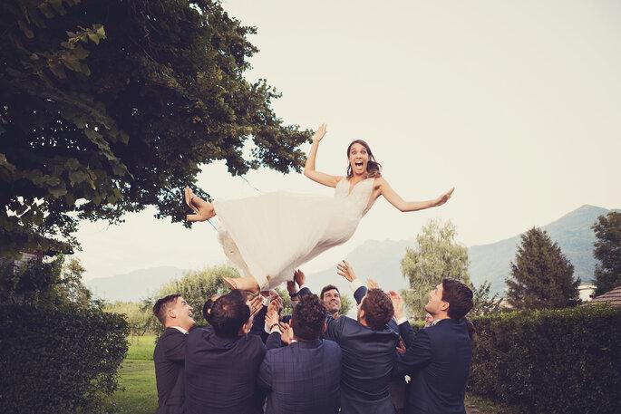 Hochzeitsfoto. Braut wird von männlichen Gästen in die Luft geworfen
