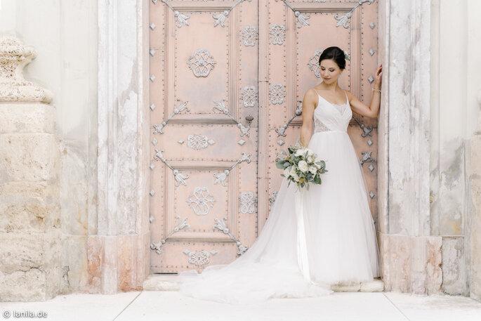 Braut vor lachsfarbener alter Tür
