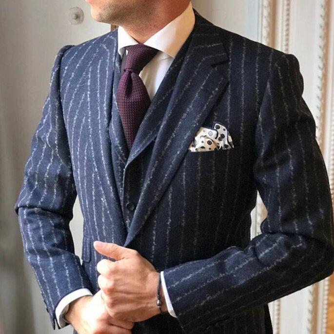 Un homme portant un costume à rayures et une cravate bordeaux, dans un style très classe et élégant.