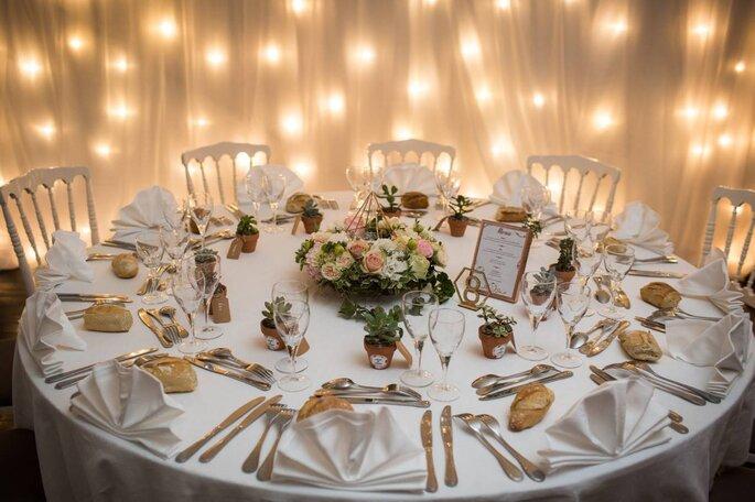 Une table de banquet de mariage joliment décorée, des fleurs en son centre et entourée de lumières.