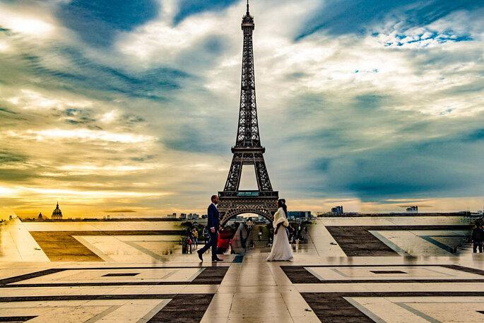 Un couple de jeunes mariés pendant une séance photo devant la Tour Eiffel