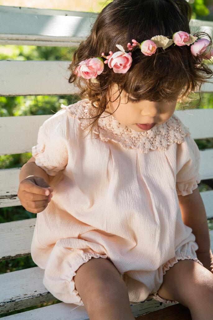 Tenue pour enfants - une fillette avec une robe rose et une couronne de fleurs, habillée pour un mariage