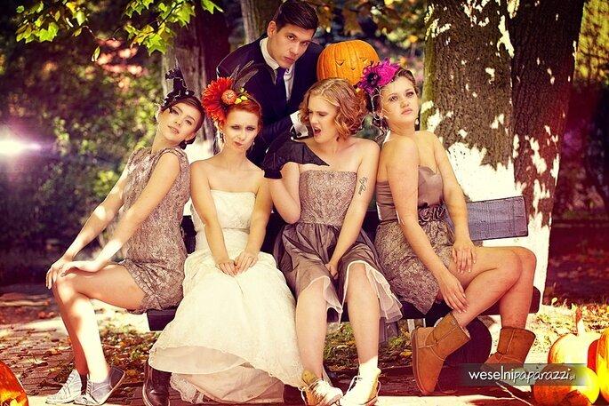 Brautpaar sitzt mit Brautjungfern auf einer Bank, alle sind im Halloween Look zu sehen