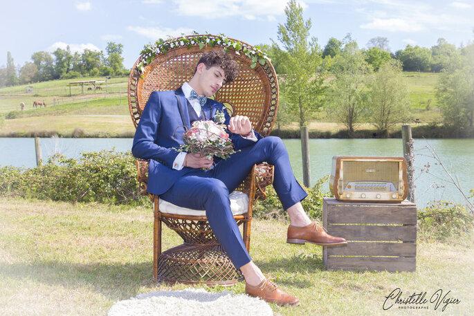 Un marié dans son costume bleu tenant un bouquet de fleurs à la main et assis dans un fauteuil Emmanuelle.