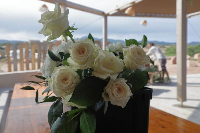 Un bouquet de roses blanches orne une table de restaurant situé face à la mer.