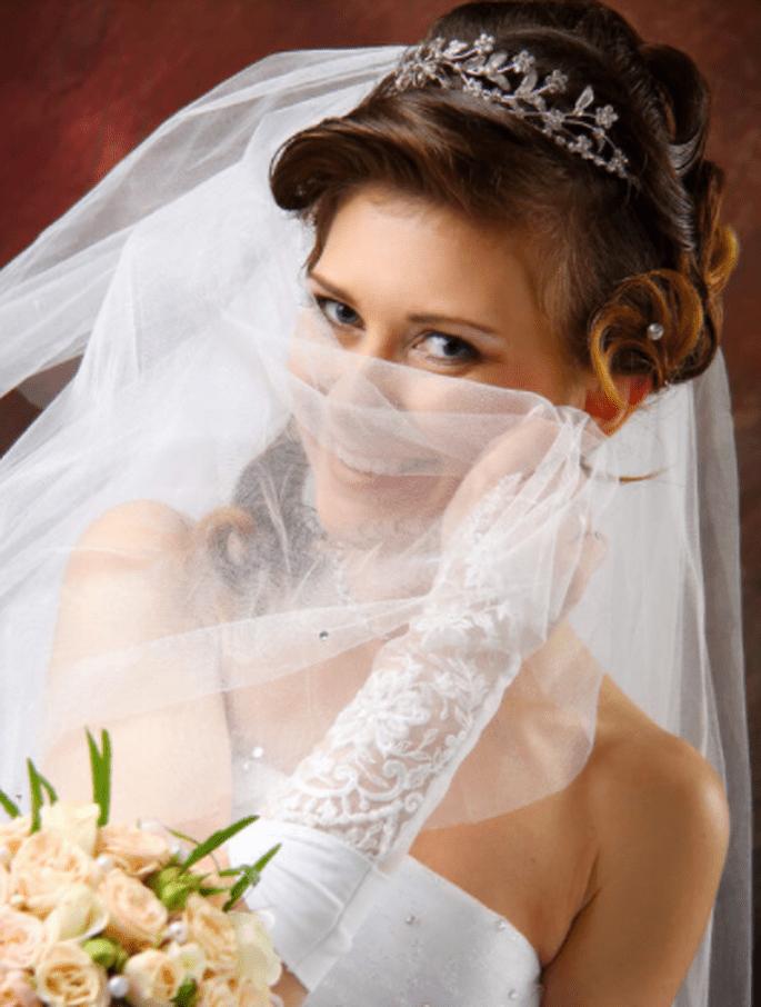Braut hält Schleier vor ihren Mund