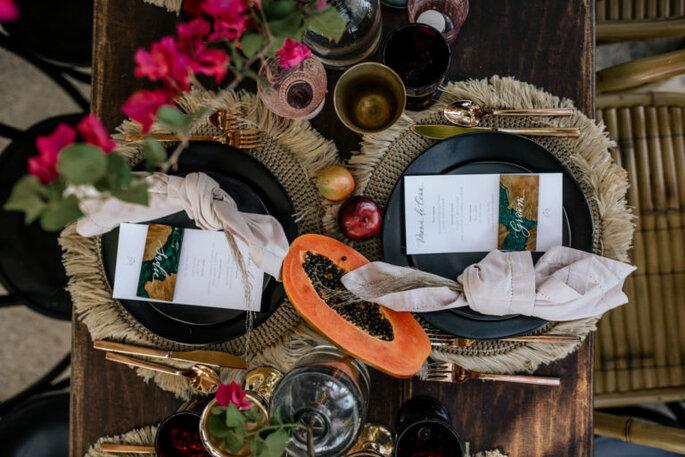 Decoración para mesas con frutas como papaya, manzana y bugambilias
