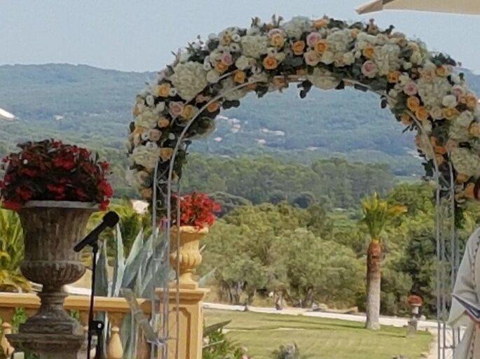 Une arche fleurie pour une cérémonie laïque en extérieur avec en arrière plan une superbe vue