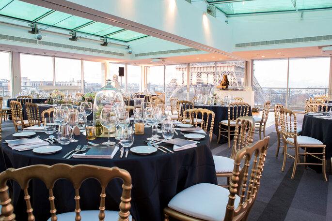 Salle de réception de mariage à la décoration noire et or au pied de la Tour Eiffel