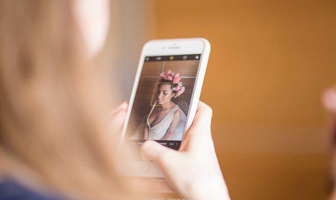 Photo sur téléphone d'une mariée portant une couronne de fleurs.