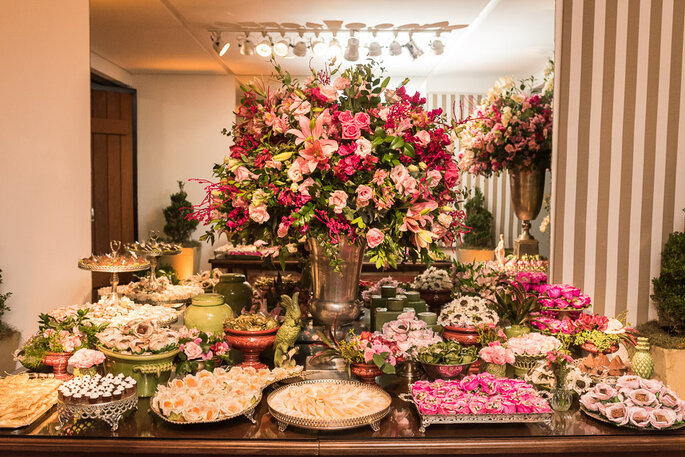 mesa de doces com pratarias e flores em rosa