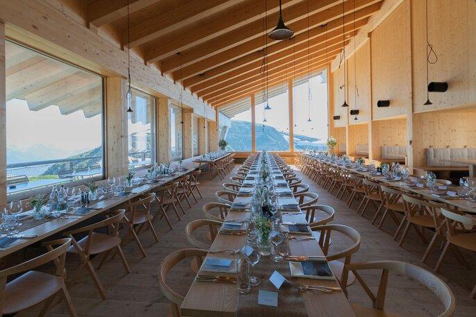 Mehrere Tische sind der Länge nach aneinander gestellt und für eine Hochzeitsgesellschaft gedeckt.