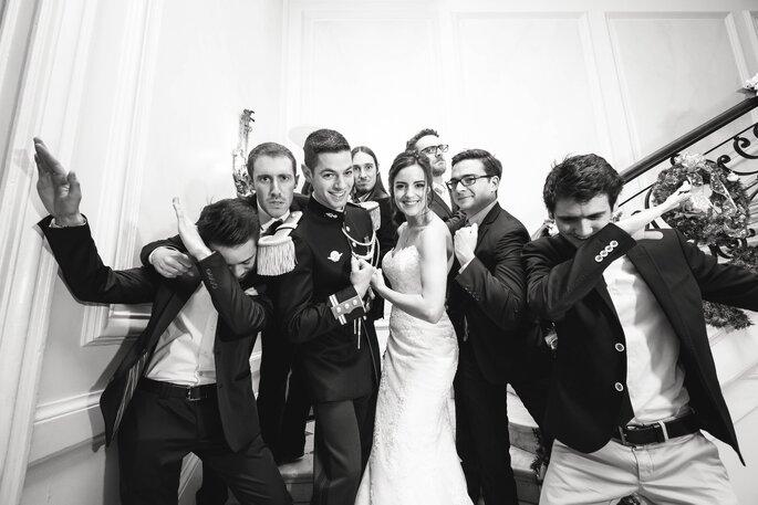 Tout un groupe d'invités en train de faire une pause en entourant les mariés sur un escalier au Château de Santeny