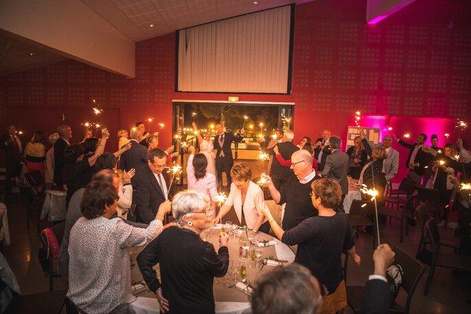 Les invités trinquent aux jeunes mariés, des bâtons d'étincelles à la main