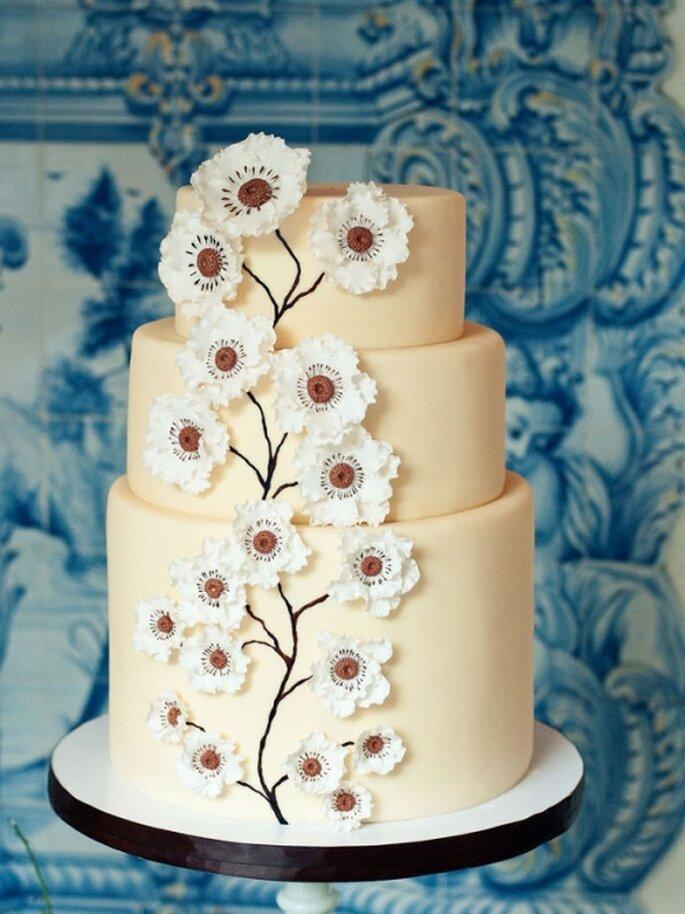 Pastel de boda color marfil, con decoración de flores de cerezo