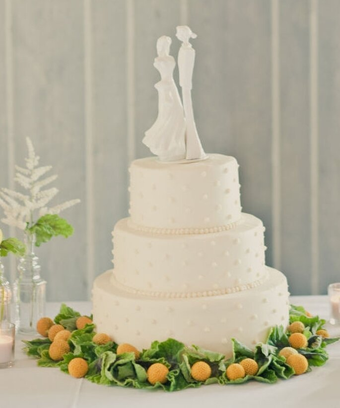 Pastel de boda blanco, con decoración inferior de flores naturales y silueta de personajes