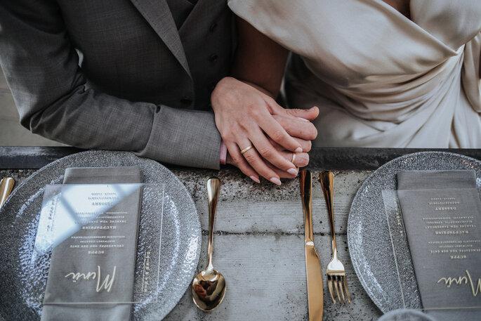 Das Brautpaar sitzt am dekorierten Hochzeitstisch und hält sich an den Händen, organisiert von Freakin' Fine Weddings.