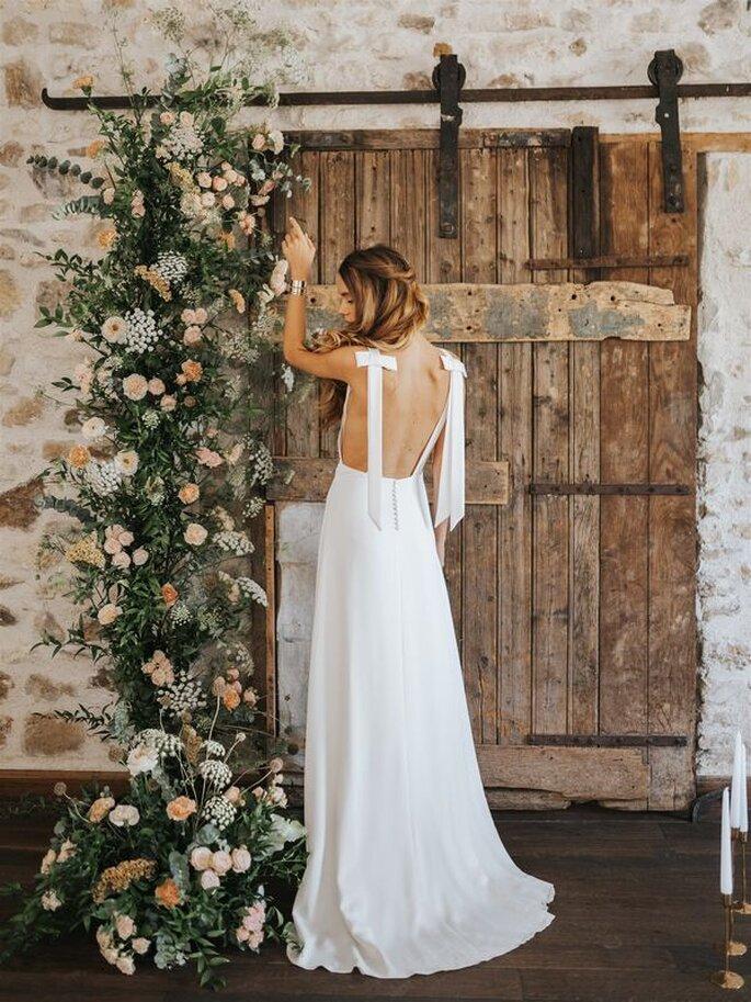 Une mariée avec une robe longue, à noeud et un dos nu pour un mariage champêtre