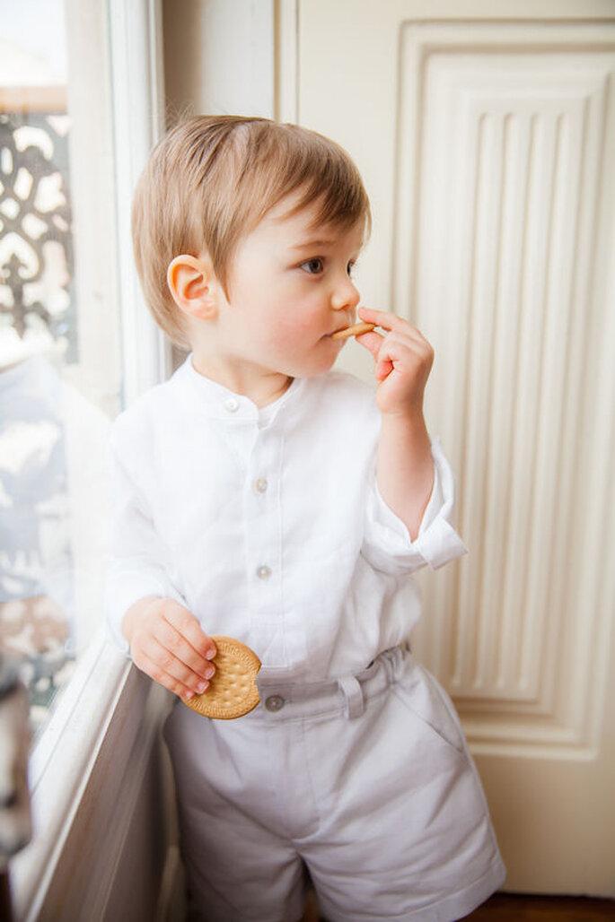 menino com calção e camisa cores neutras a comer uma bolacha