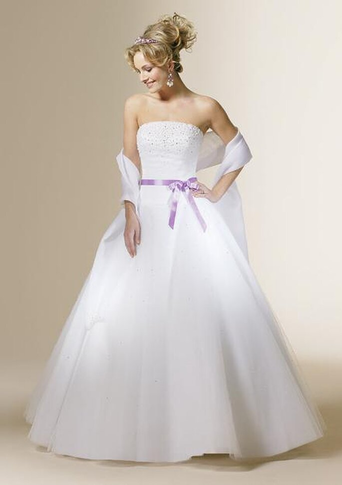 Si te han encantado los vestidos lila, pero piensas que no te sentirías cómoda en tu boda con un traje íntegramente de ese color, puedes darle un toque de lila a tu vestido blanco en un delicado lazo e imperceptible bordado en la parte superior. Delicado y hermoso. Puedes complementar con un ramo de diminutas rosas lila y diadema en este color.