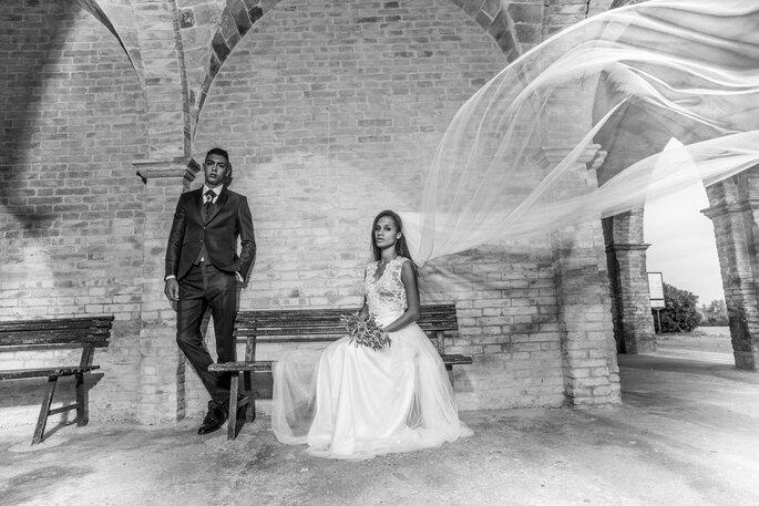 Ein Brautpaar sitzt vor einer Backsteinmauer. Der Schleier der Braut fliegt im Wind.