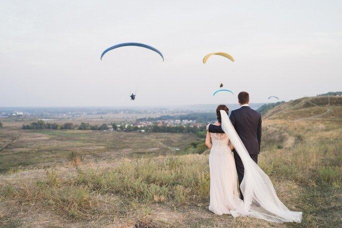 Recién casados observando parapentismo