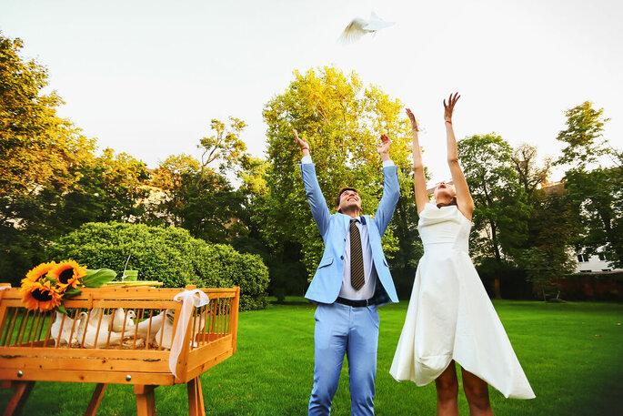 Brautpaar wirft Brautstrauß in die Luft.
