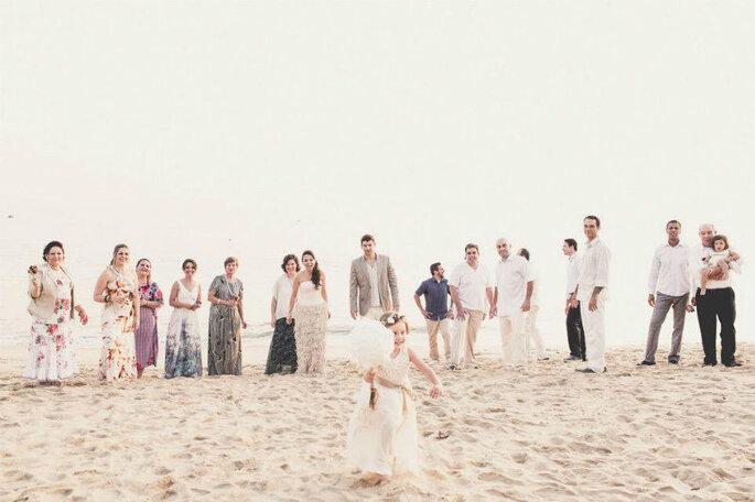 Foto de família na praia, após o casamento e daminha correndo com algodão doce na mão.