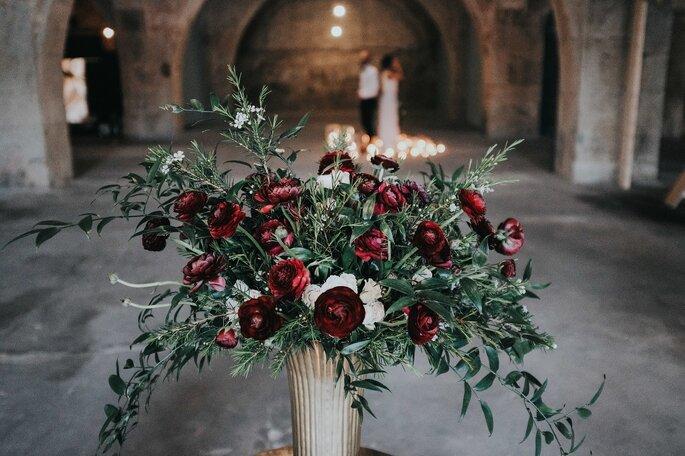 vaso com folhagens e rosas vermelhas noivos ao longe com velas