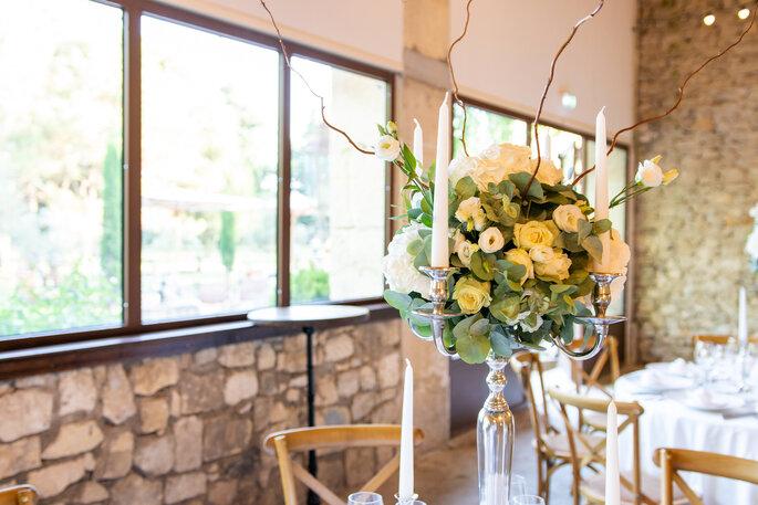 Tables d'une réception de mariage ornées de chandeliers garnis de roses