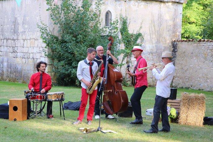 Un groupe de jazz élégant anime un cocktail de mariage en extérieur