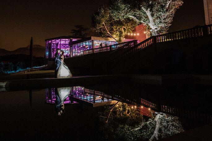 Deux mariés en train de s'enlacer dans la nuit, au bord de la piscine du Château de la Roque Forcade, illuminés par la verrière
