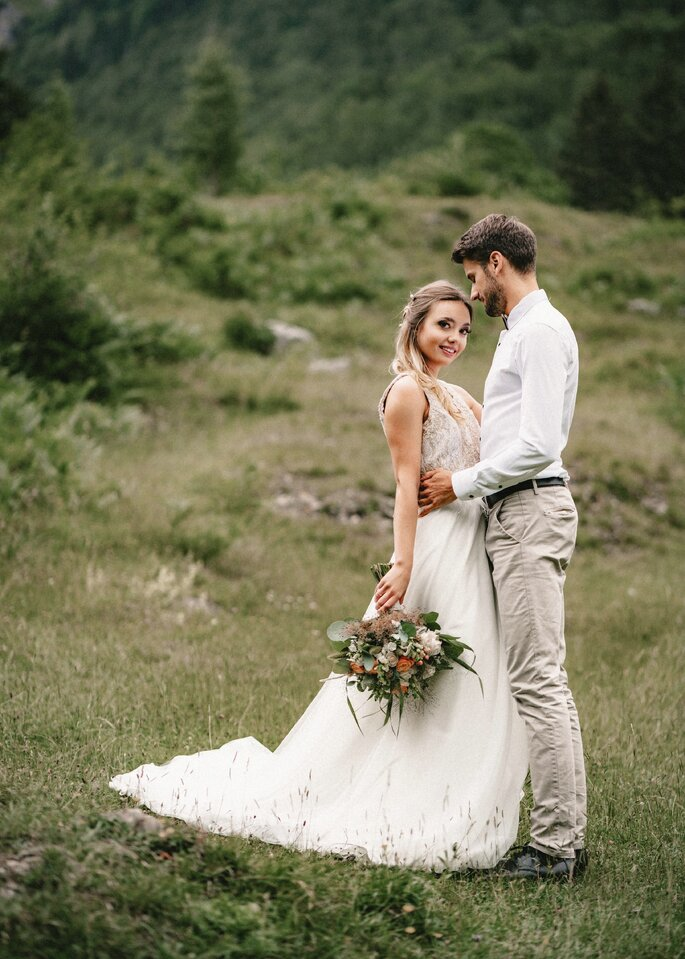 Brautpaar steht in grüner Natur. Bräutigam sieht seine Braut verliebt an.