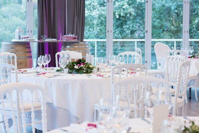 Salle de réception d'un mariage aux tables décorées avec soin et aux grandes baies vitrées
