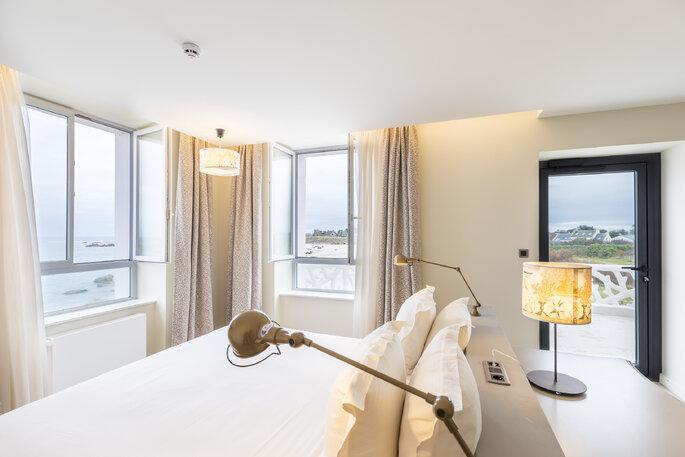 Hôtel de la Mer, chambre avec un lit et des rideaux blanc avec vue sur l'océan