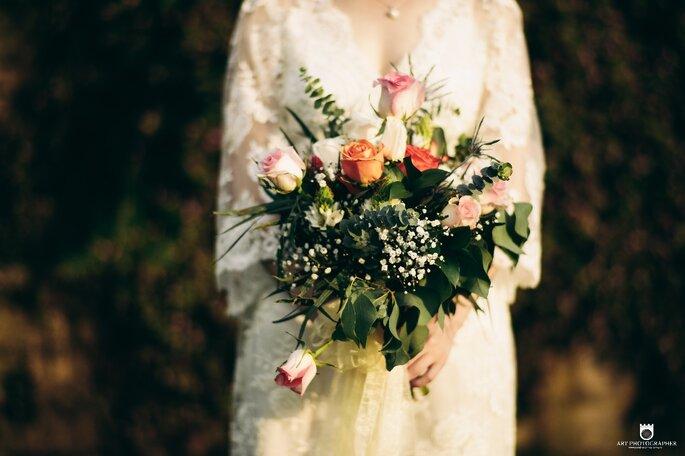 Novia sosteniendo ramo de novia con follaje