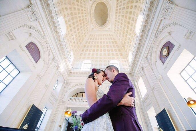 Un couple de mariés s'enlace au milieu d'une grande salle a haut plafond. La photo est prise en contre-bas.