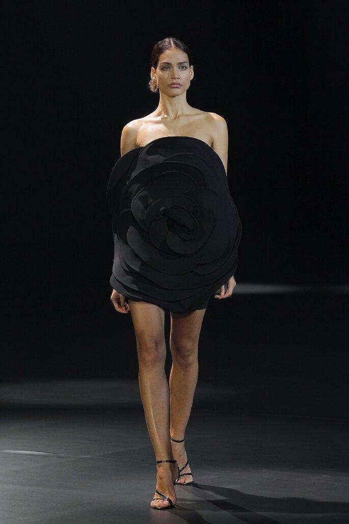 Vestido de fiesta corto color negro con escote palabra de honor con una flor grande