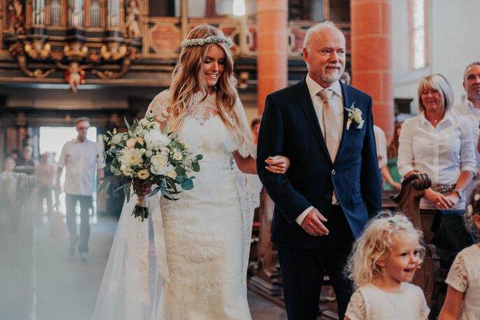 Die Braut wird von ihrem Vater zum Traualtar geleitet.