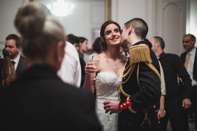 Couple se mariant dans un château, une coupe de champagne à la main et un baiser dans le cou