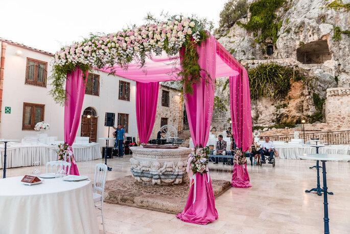 Une superbe arche avec des tentures roses et des fleurs disposée au centre de tables de mariage