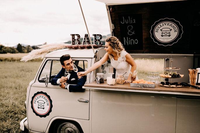 Bräutigam sitzt am Steuer und seine Frau reicht ihm über den Tresen ein Glas Champagner