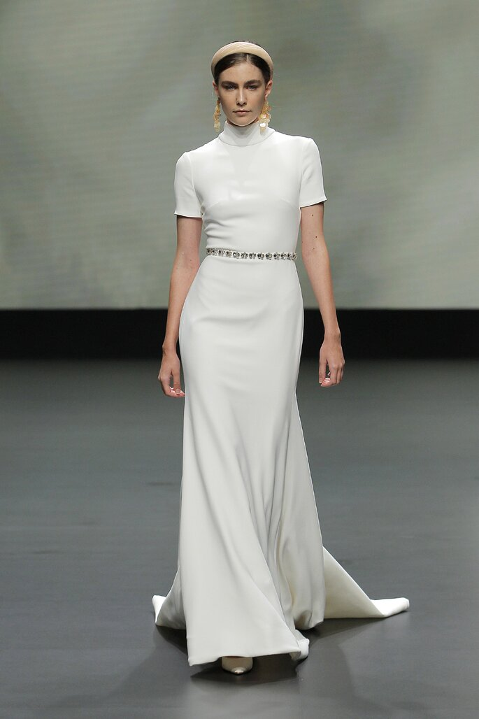 Vestido de novia con corte de sirena con cola corta, cinto de pedrería sencillo, mangas cortas y cuello alto
