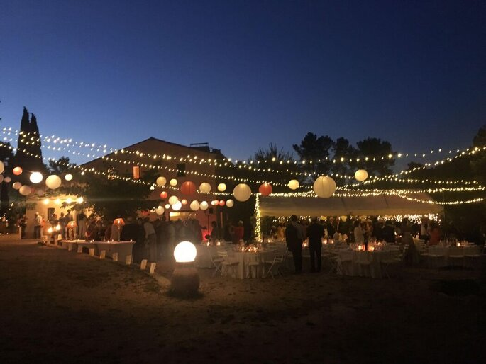 Une réception de mariage à l'extérieur avec une belle décoration et des guirlandes guinguettes qui s'illuminent à la nuit tombée