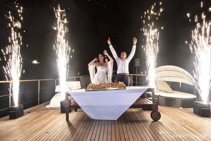 Deux mariés à bord du Yacht Clara One attendent avec enthousiasme l'arrivée de la pièce montée